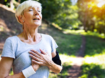 elderly woman experiencing chest pain while in the woods taking a walk